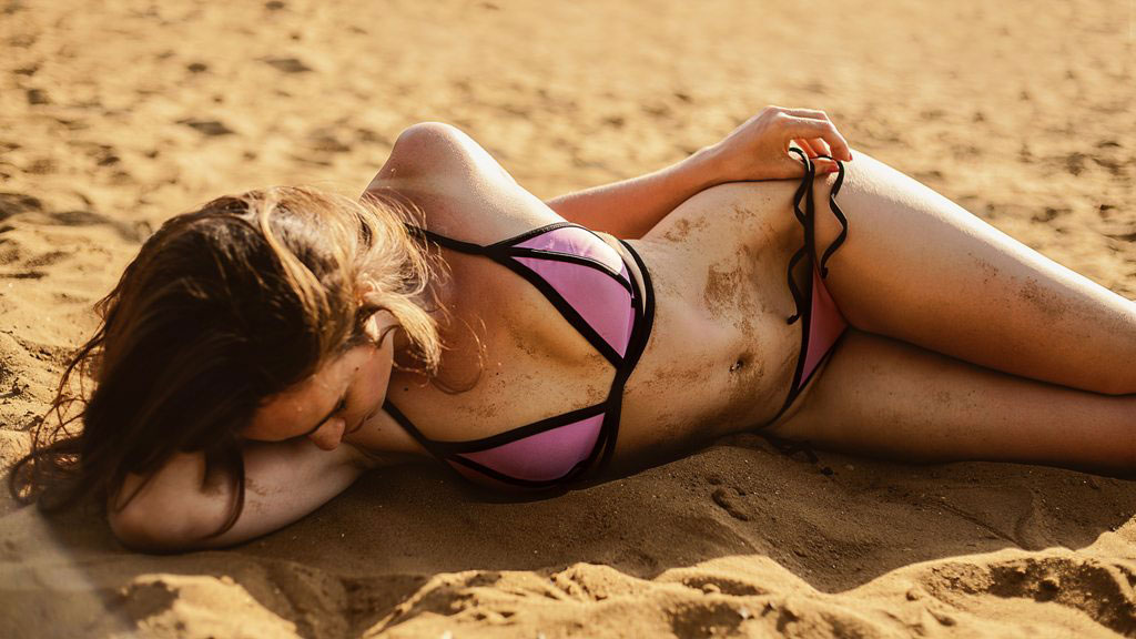 woman laying down in the sand in a bikini