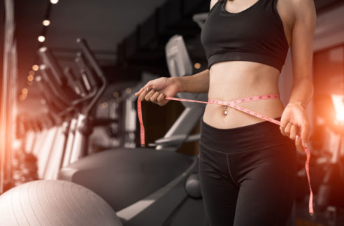 Sporty Woman Using Waist Tape Line Stock Photo