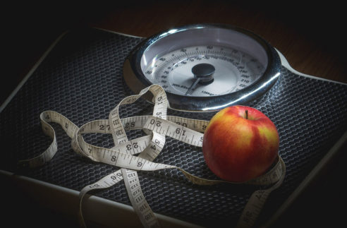 Scale with a waist ruler and an apple