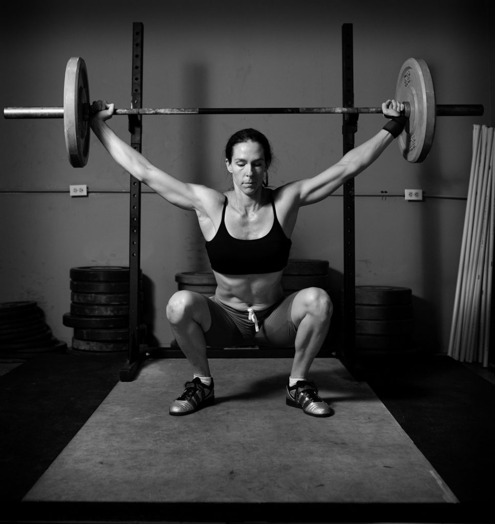 Black and white photo of woman lifting weights