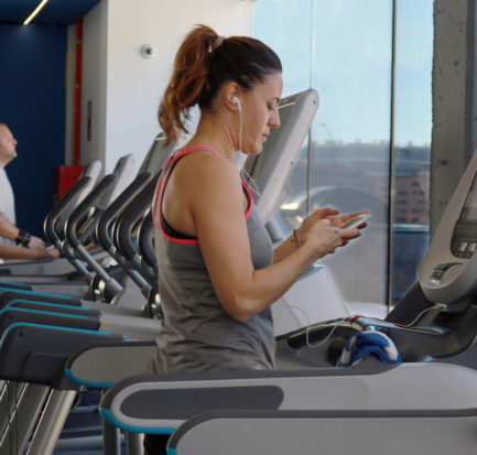 Woman looking at her phone while on a treadmill