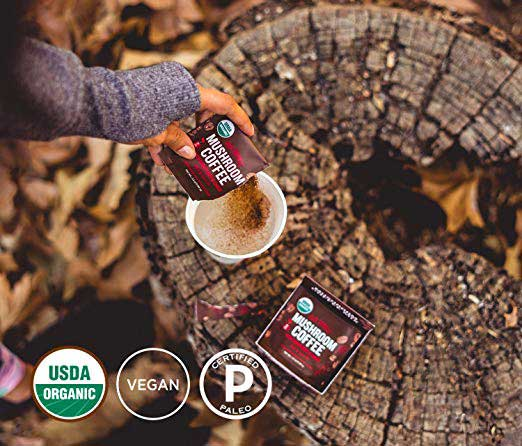 Woman in the woods putting Four Sigmatic in a cup
