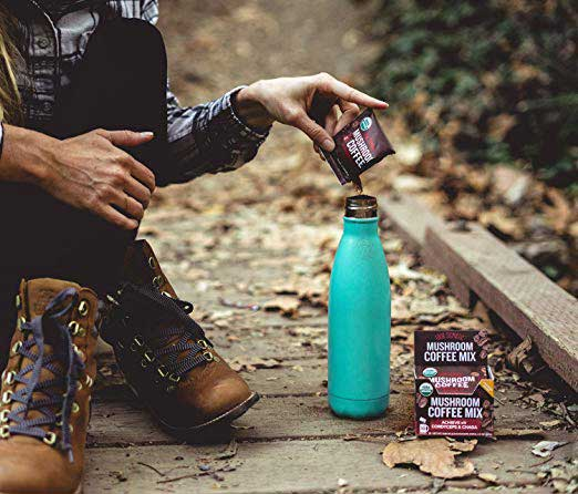 woman in the woods putting Four Sigmatic in a water bottle