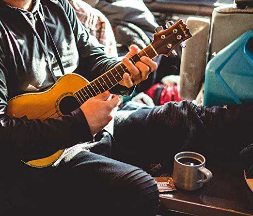Man playing guitar with a cup of coffee