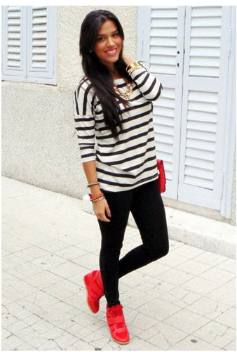 girl wearing black and white blouse, black pants, and red shoes with a red purse