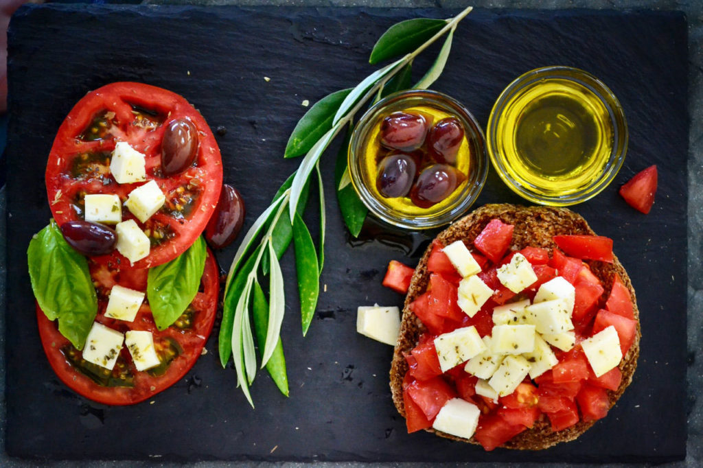 photo of tomatoes, olives, feta cheese, and olive oil