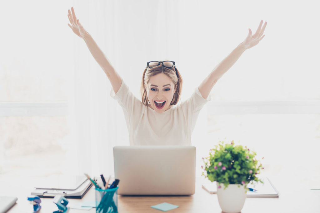 Happy excited successful businesswoman triumphing with laptop