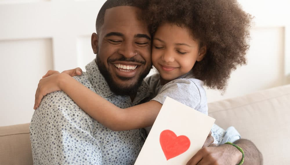 Happy Affectionate African American Dad Embracing Stock Photo
