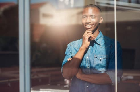 oung African Designer Looking Through Window Stock Photo