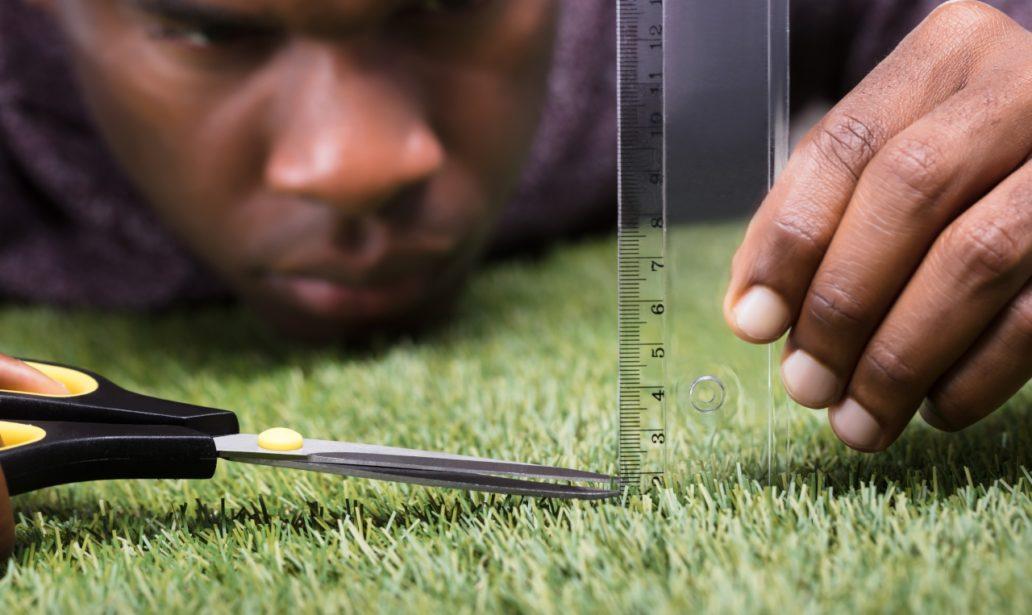 Closeup Man Cutting Green Grass Measured