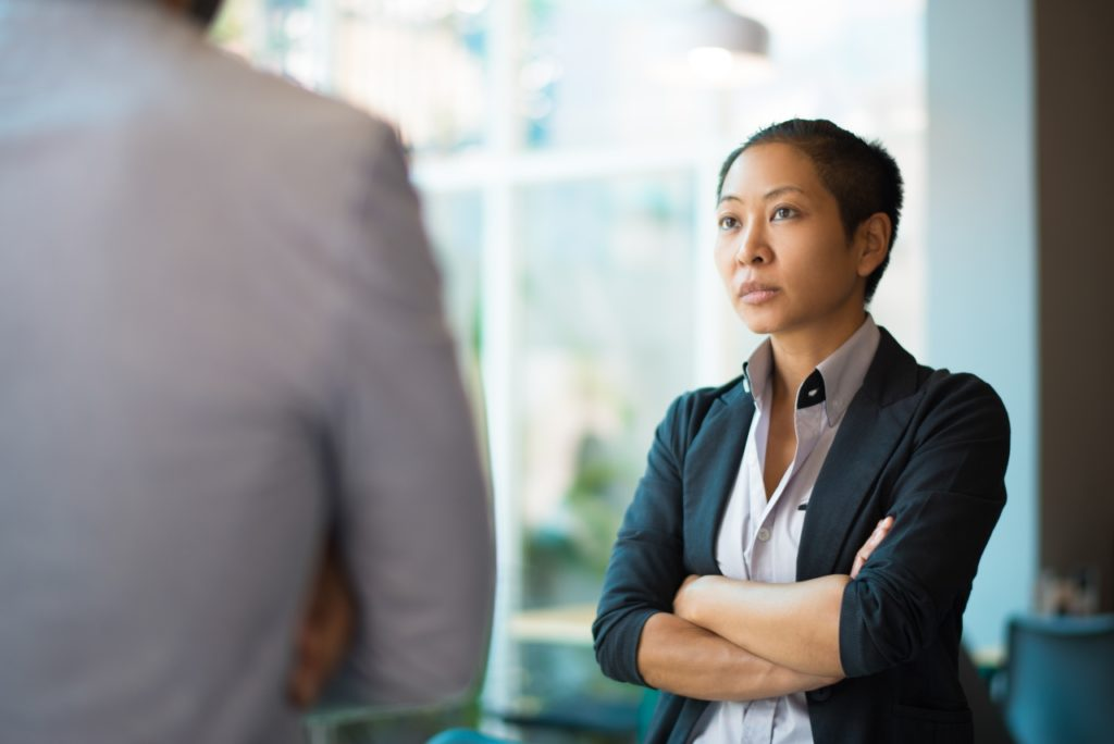 Tense Asian Businesswoman Looking at Male Partner