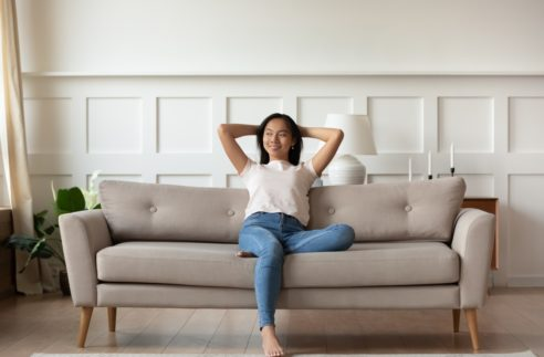 Asian woman looks at distance resting leaned on couch enjoy fresh air in summer day in modern fashionable living room interior, full length image. Contemporary apartments owner or carefree day concept
