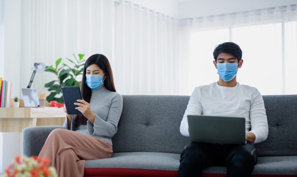 Lovers working in the house Use Social Distancing and put on a mask to protect against viruses. Concept Work at home