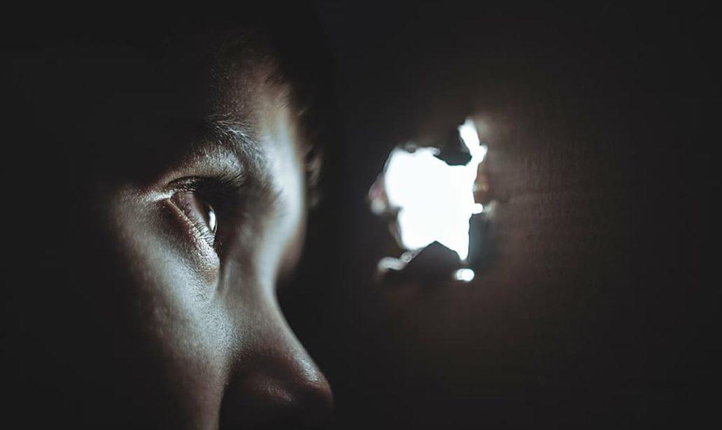 boy peeking through a hole