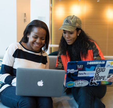 two black women chatting on a couch with their laptops
