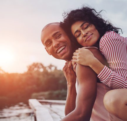 Happy moments together. Happy young couple embracing and smiling while sitting on the pier near the lake