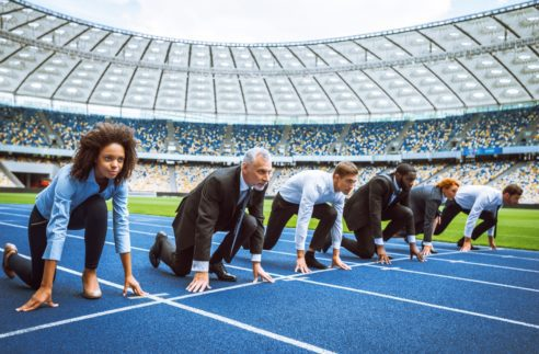Side view photo of confident multi ethnic business people lined up getting ready for race on modern sport track. Stadium as a background