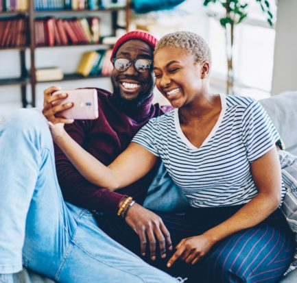 Cheerful dark skinned couple in love resting at home interior posing for selfie on smartphone camera,happy young hipsters making image on modern mobile phone laughing at living room together