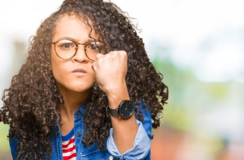 Young beautiful woman with curly hair wearing glasses angry and mad raising fist frustrated and furious while shouting with anger. Rage and aggressive concept.