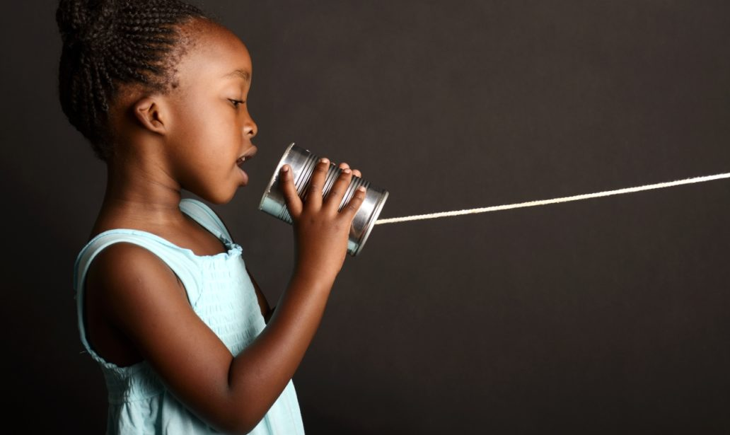 African girl communicating through a tin
