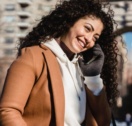 smiling female standing on street and talking on smartphone