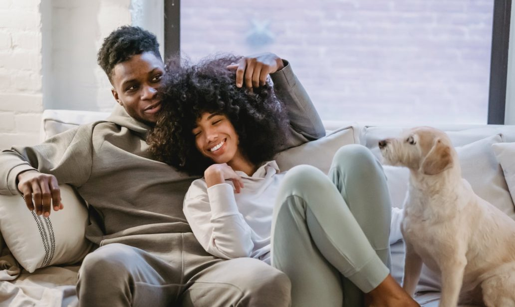 romantic black couple chilling on couch with dog