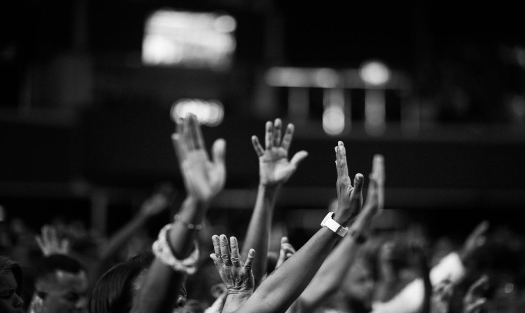 grayscale photography of people raising hands