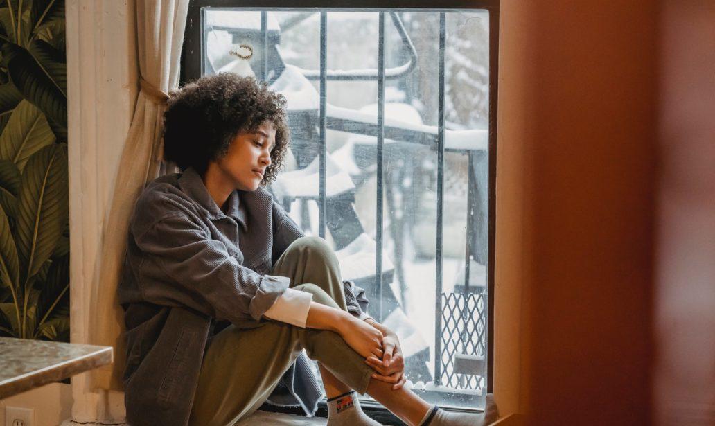 melancholic black female sitting on windowsill